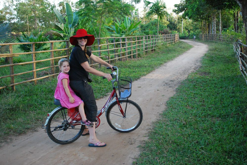 mom and daughter on bicycle on green path on Don Daeng island Thailand