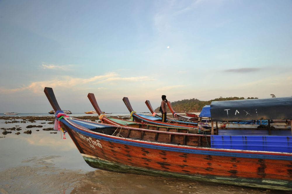 colorful wooden boats lined up on the beach at Koh Lanta island Thailand