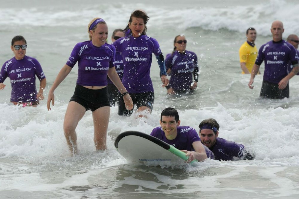 Volunteer surfers enabling paraplegics to surf as part of the nonprofit Life Rolls On program.