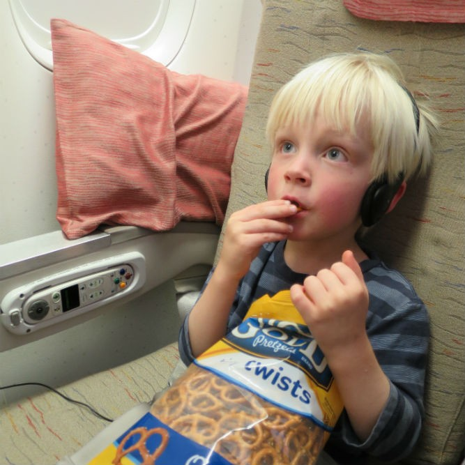 kid eating pretzels and watching TV on a plane