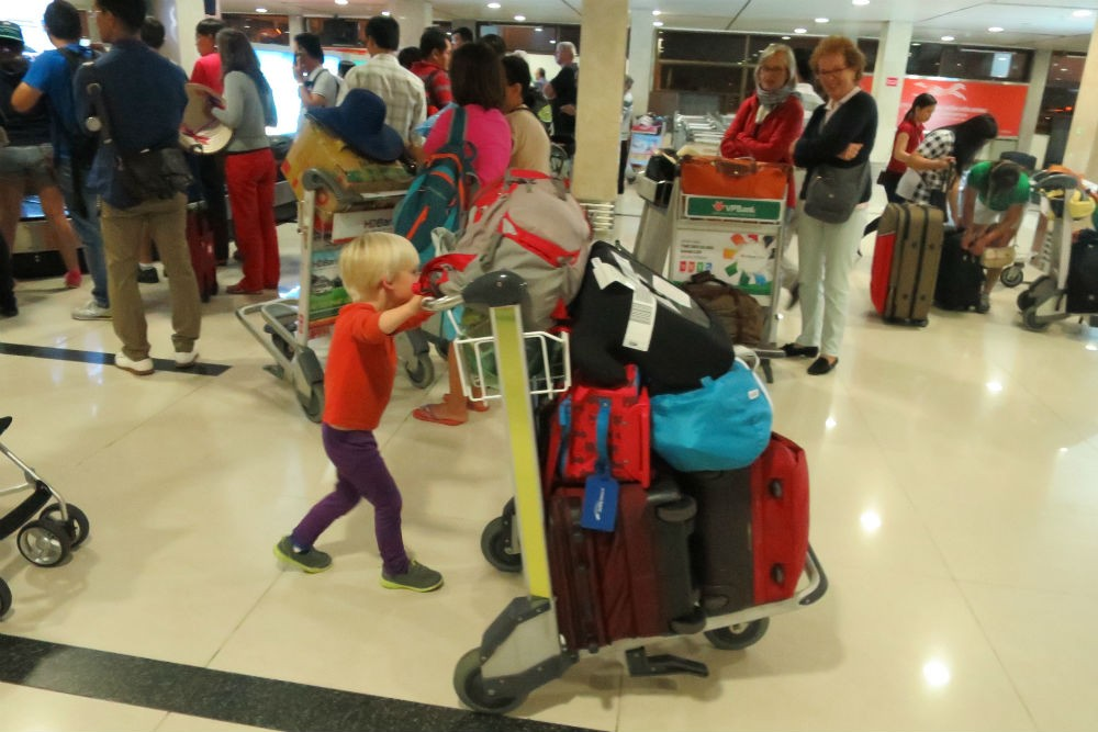 kid in airport pushing luggage cart