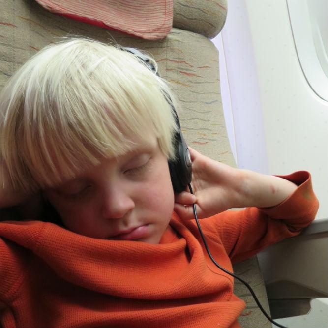 kid asleep in airplane seat