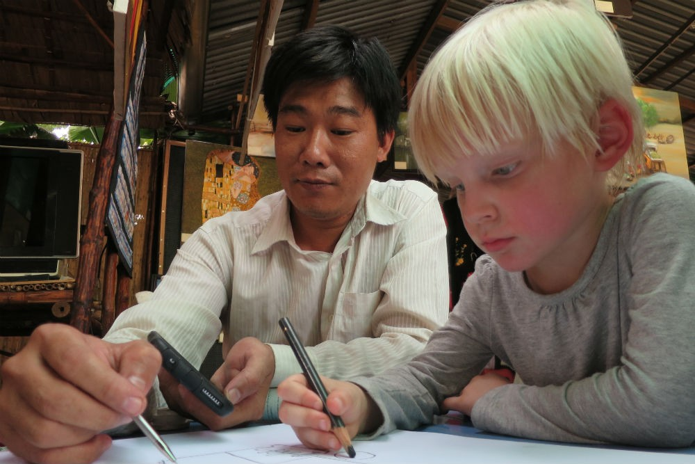 local artist and kid sketching in Mekong Delta