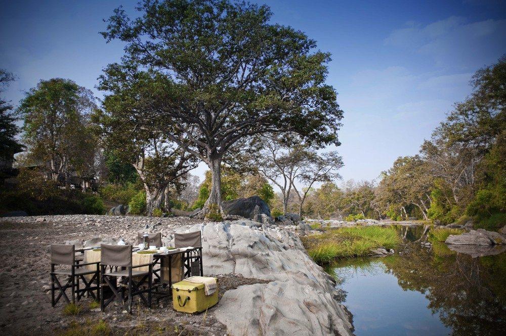 An outdoor dining experience at Banjaar Tola, a safari lodge in Kanha National Park, India.