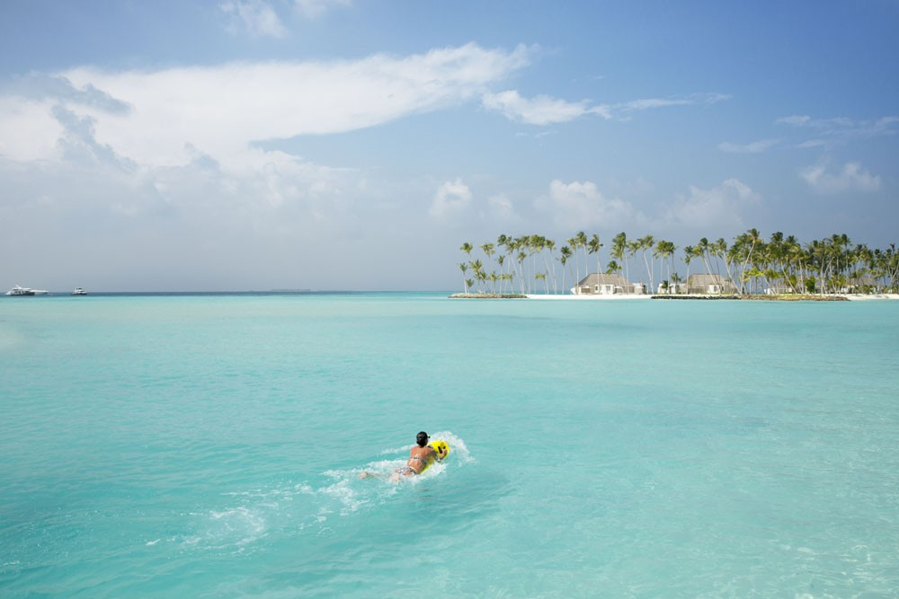 person swimming in clear blue water at Cheval Blanc Randheli resort in the Maldives