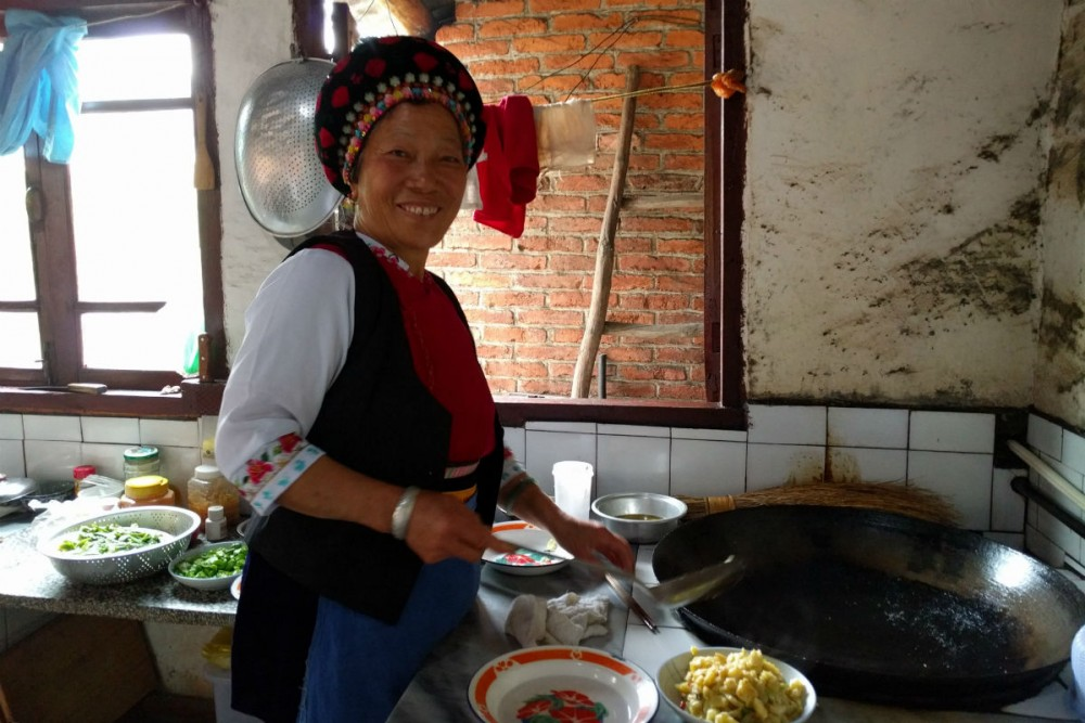 Bai minority woman cooking lunch in Yunnan Province China