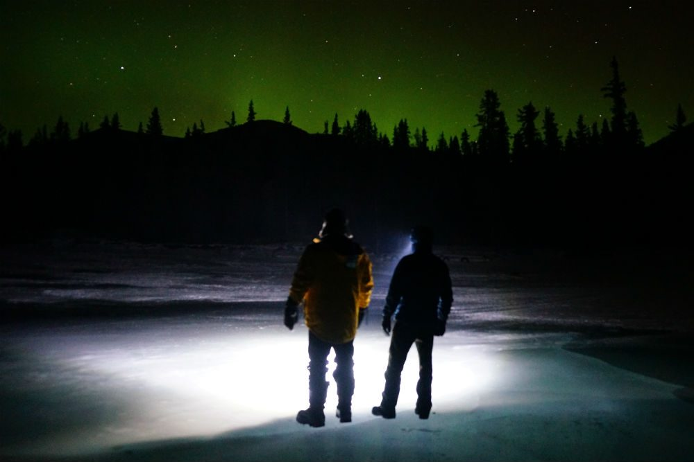 two people watching the northern lights in british columbia canada