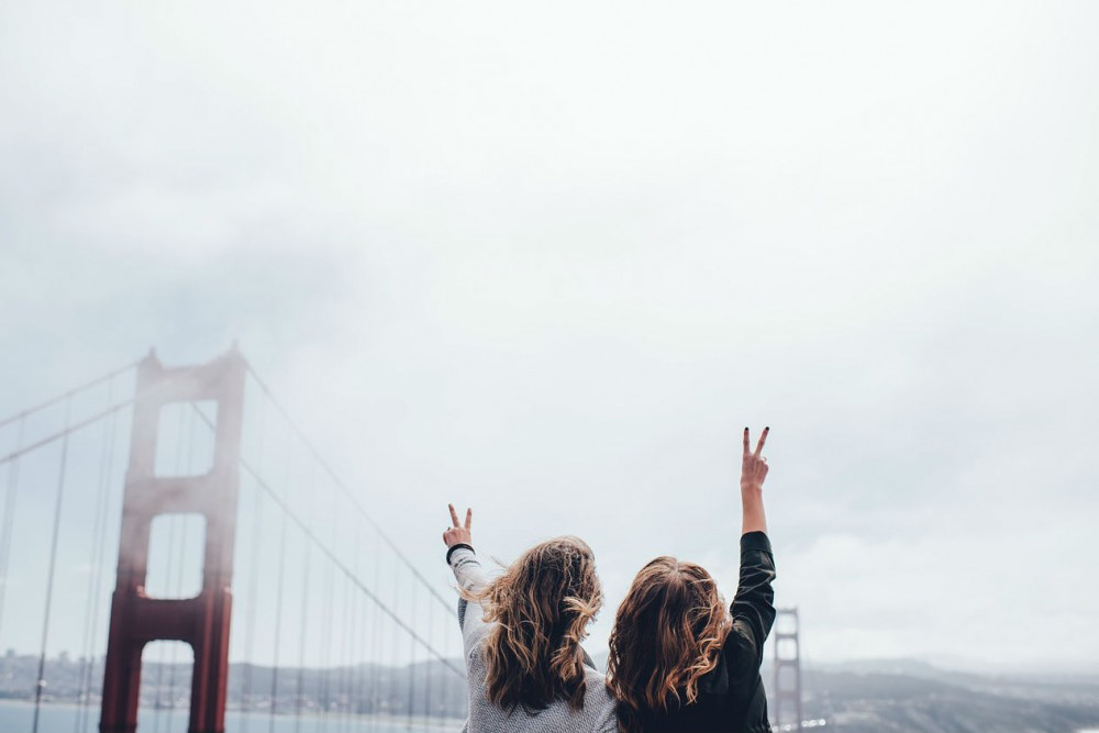 women giving peace sign at Golden Gate Bridge, California