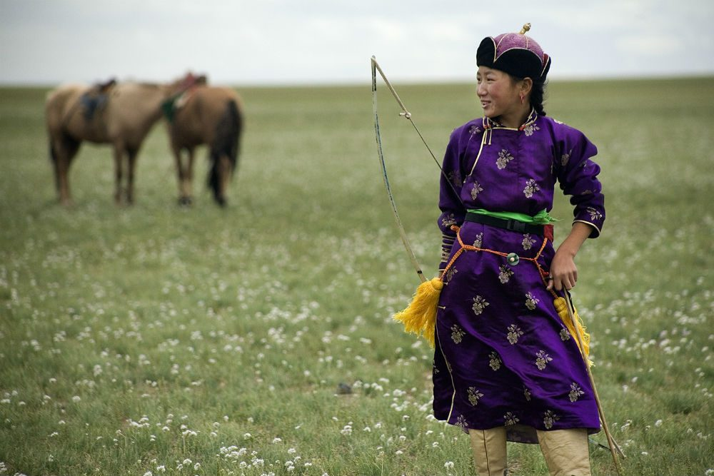 Naadam archer, standing in field with horse in Mongolia