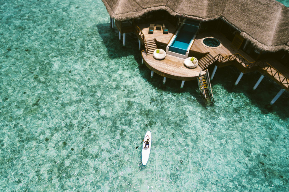 aerial view of an overwater bungalow at Huvafen Fushi in the Maldives