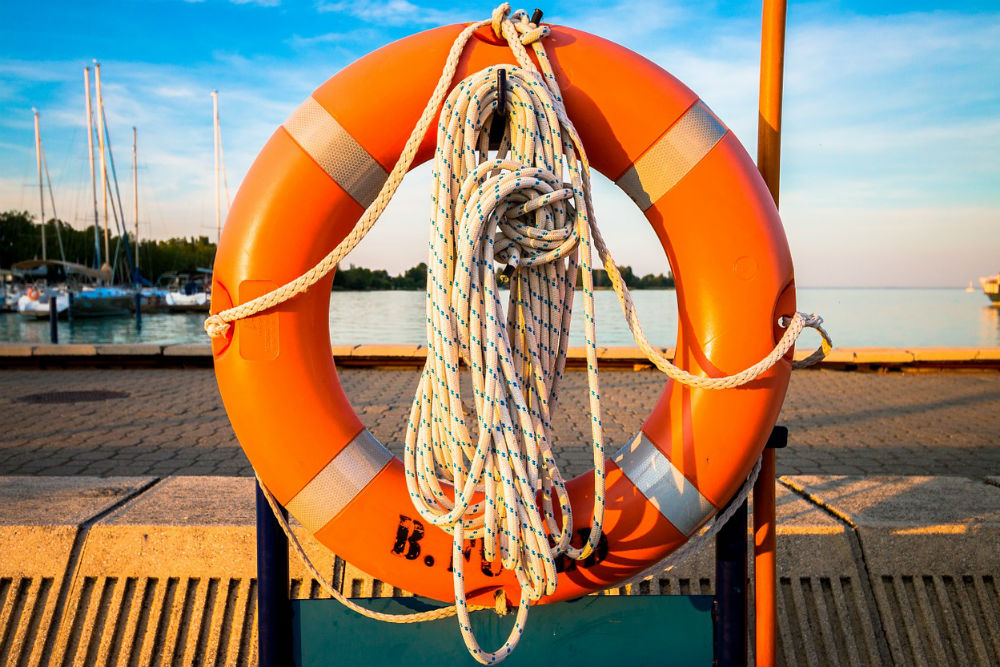orange life preserver on hook at lake