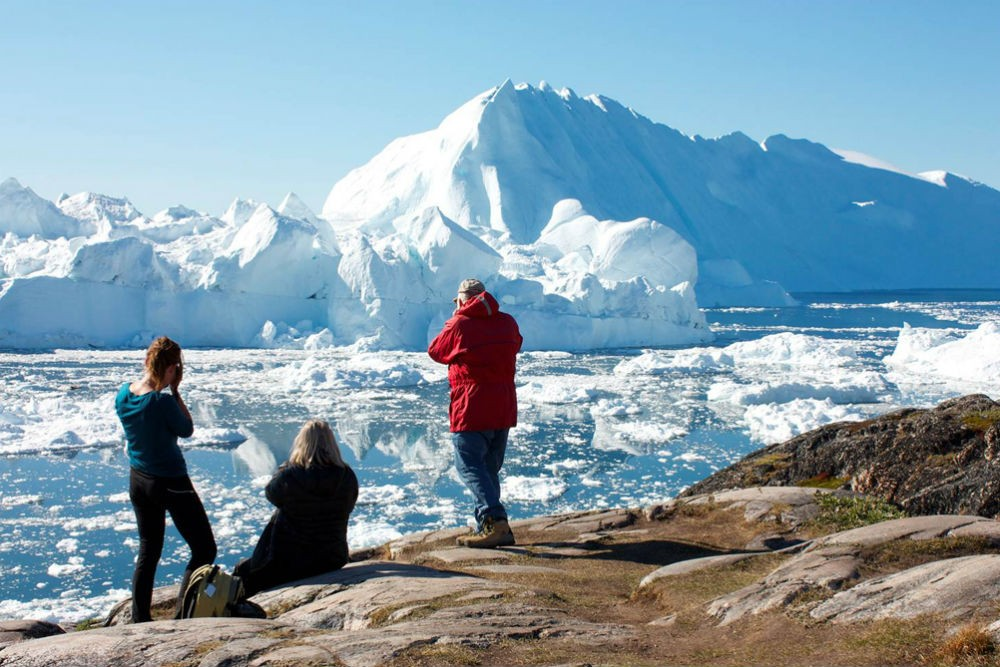 people taking pictures of an iceberg in greenland