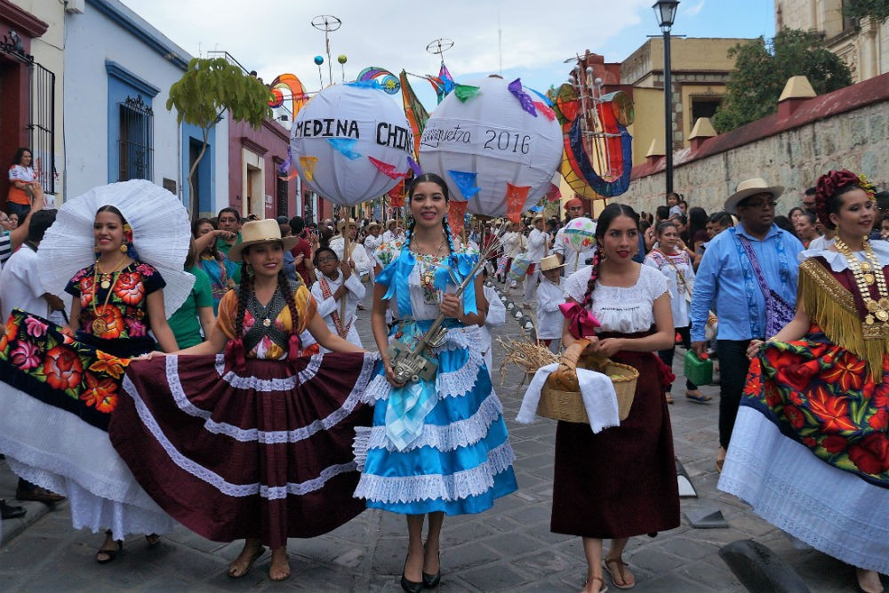 people parading in Oaxaca street for La Guelaguetza, one of Mexico's most colorful festivals