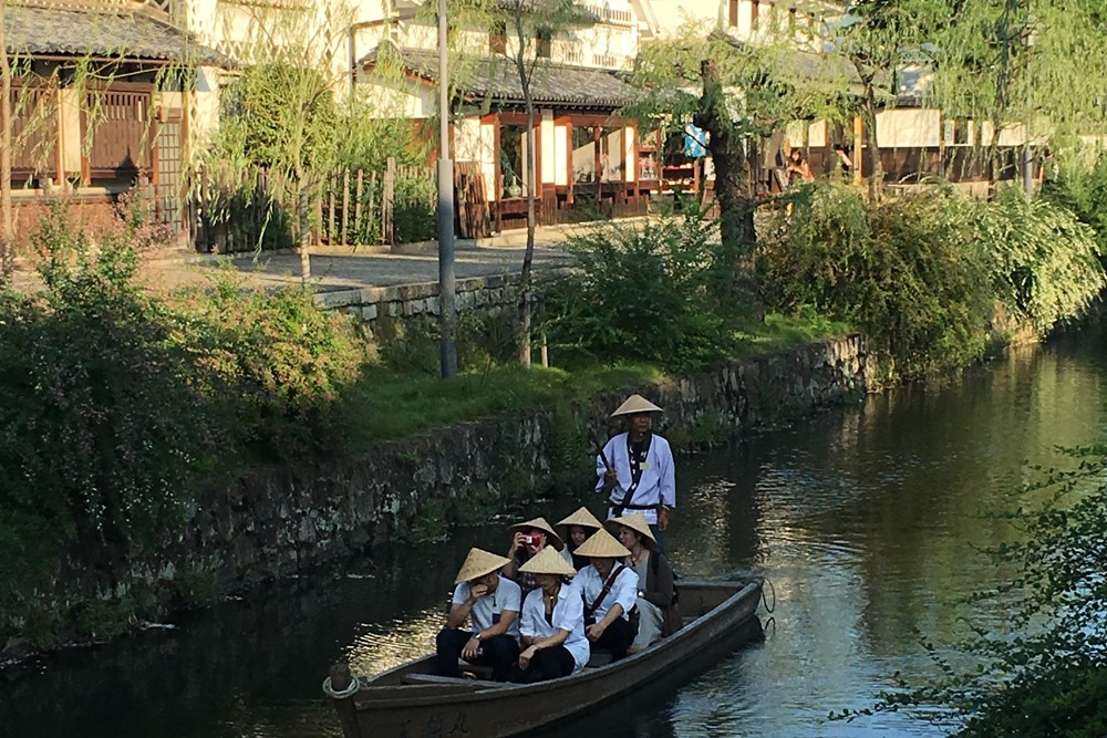 men in conical hats poling a boat down a river in Kurashiki Japan