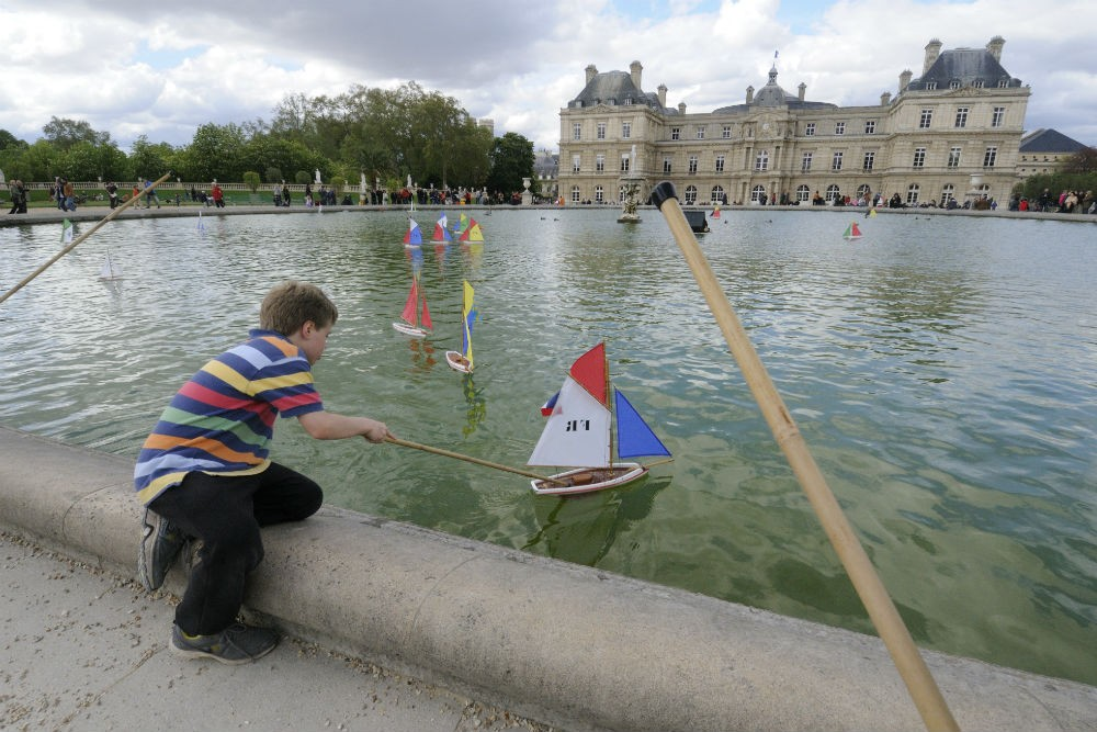 child playing with toy boats in the Jardin du Luxembourg, Paris France
