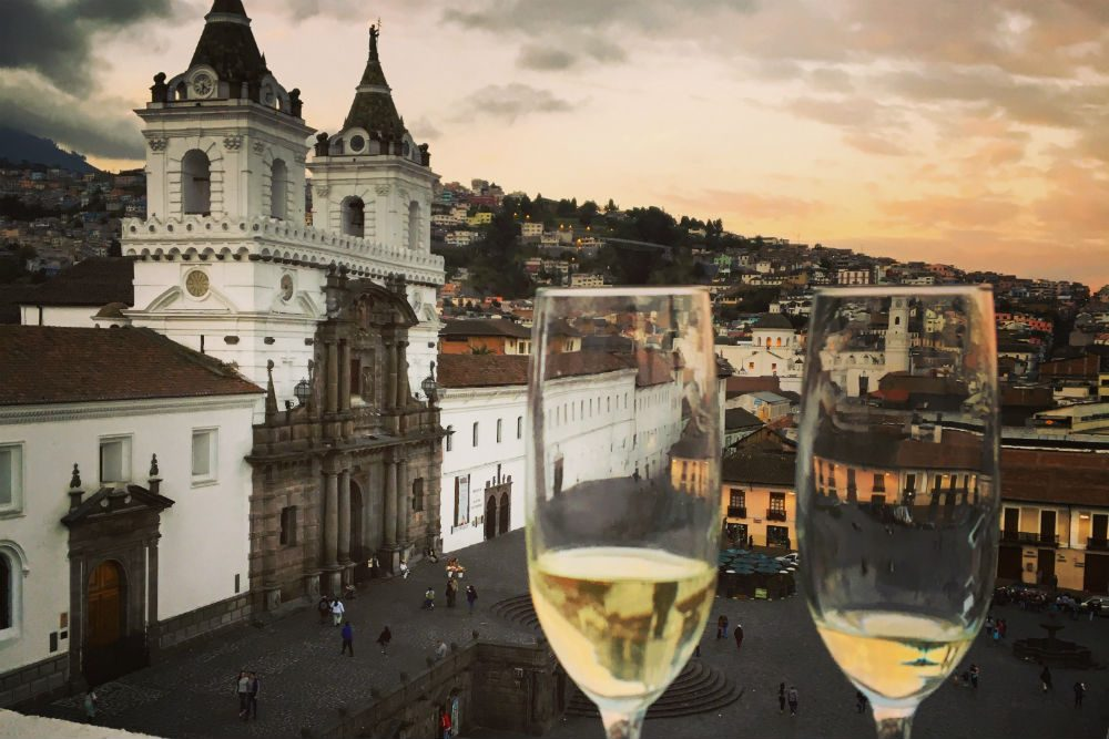 San Francisco Plaza in Quito Ecuador, with 2 wine glasses in the foreground overlooking the city