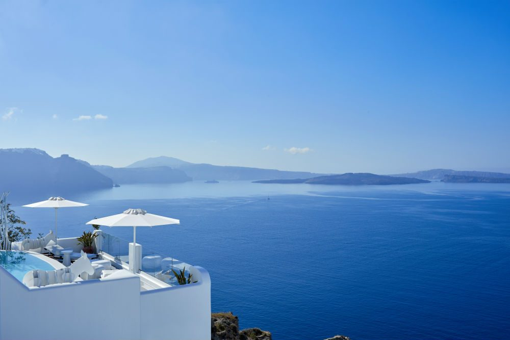 white hotel room deck overlooking the blue ocean on Santorini island Greece