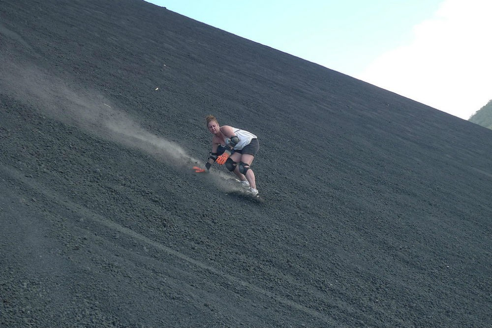 woman sandboarding down the Cerro Negro volcano