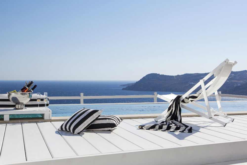 beach chairs by the pool Myconian Villa Collection Myconian Villa Collection in Mykonos Greece