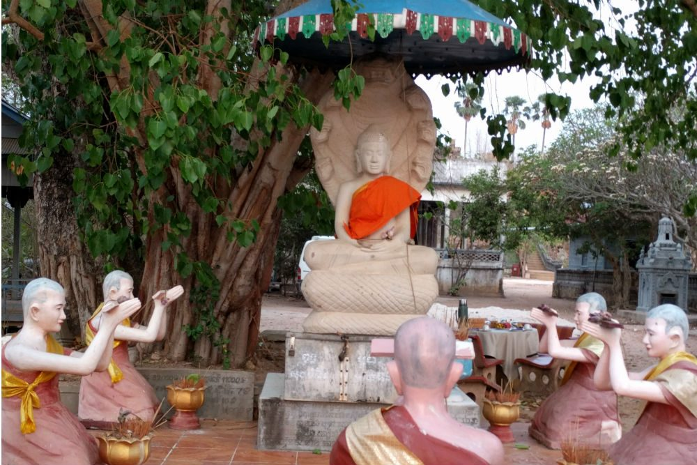 buddha statue with monks and a banyan tree at Phnom Krom temple in Cambodia