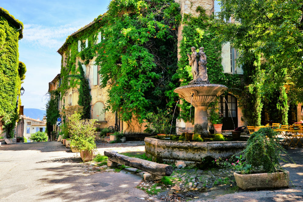 Leafy town square with fountain in a picturesque village in Provence, France