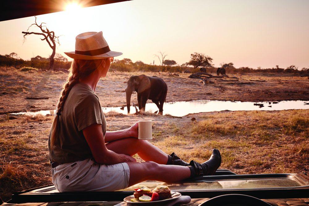woman drinking coffee in Botswana plains with elephants at watering hole nearby
