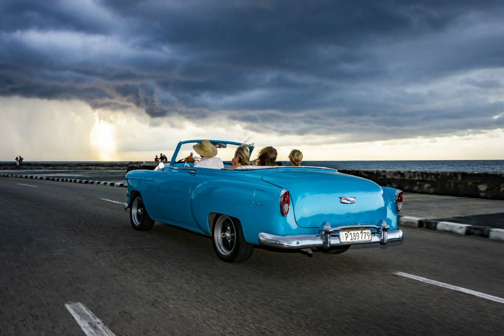 people in old fashioned car driving on open road in Cuba