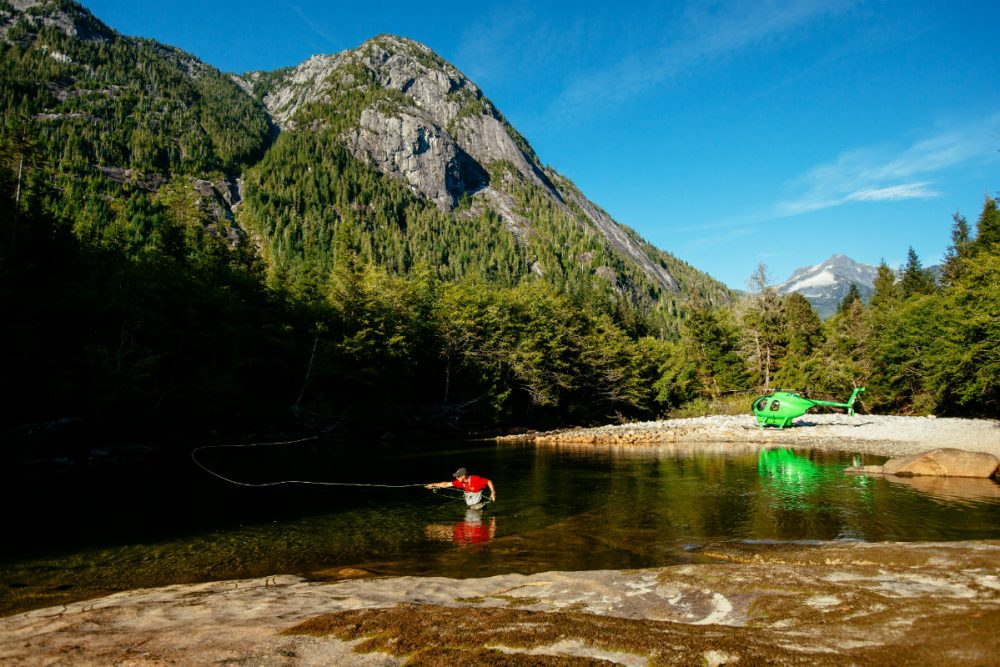 fisherman in a river with a helicopter parked nearby in the mountains of British Columbia Canada