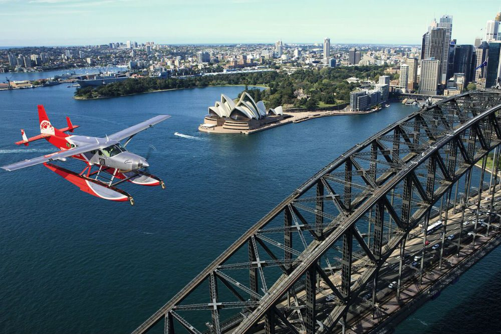 seaplane flying over Sydney Harbour with bridge and opera house