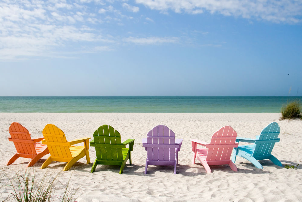 Colorful empty adirondack Chairs lined up on a sunny Beach