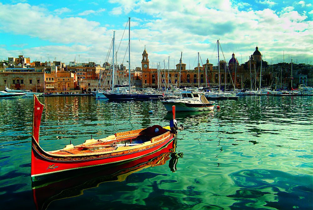 a dgħajsa, or a traditional water taxi, in the water off Vittoriosa Malta