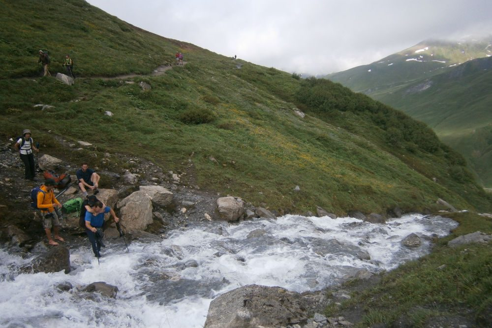 Crossing a stream on the Tour de Mont Blanc hiking trail