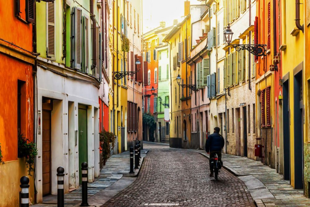 winding colorful street in Parma Italy with biker on it
