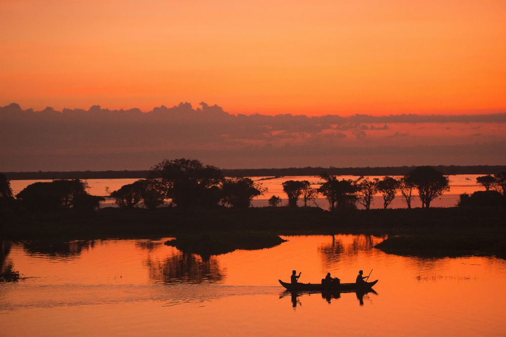 silhouette Sunrise Fisherman fishing on the boat at Tonle Sap lake Cambodia