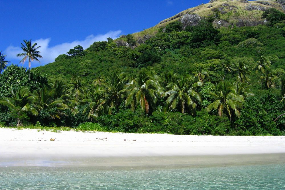 green mountain and beach with clear water on Mamanuca island Fiji