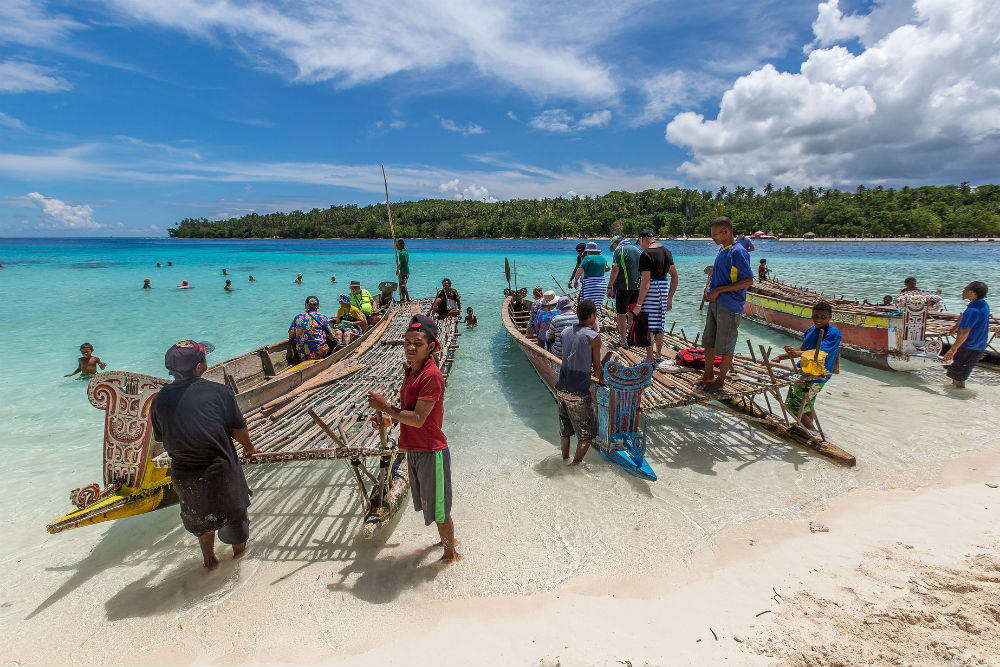 mean with lakatoi boats on beach of Papua New Guinea
