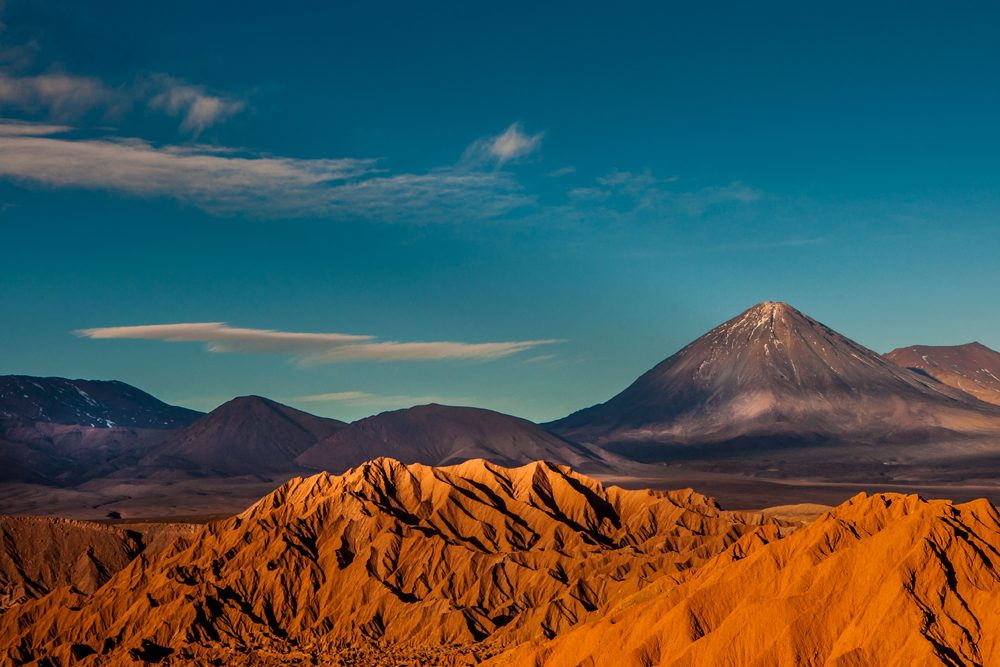 the red sand of Chile's Atacama desert with tall mountains in the distance