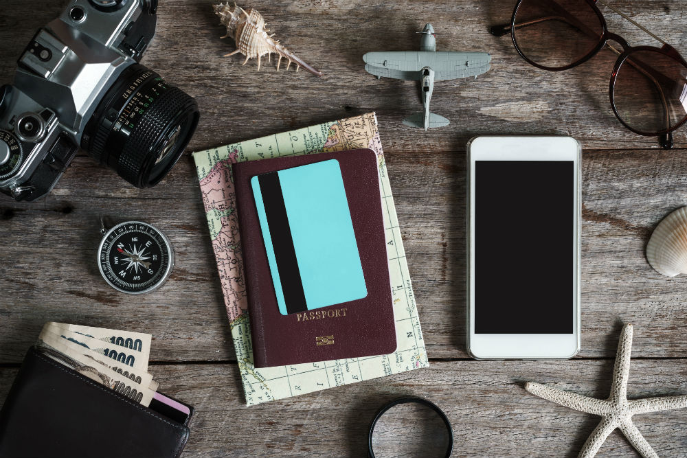 travel planning with a credit card passport map and phone on table