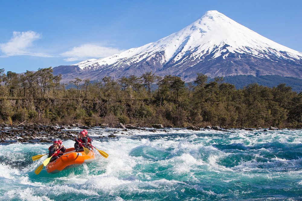 a rafting tour boat on the Petrohue River of Chile with snowcapped mountains in background