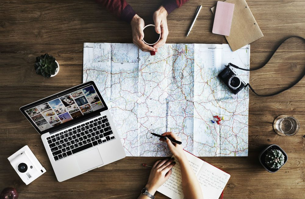 travel planning with map and laptop