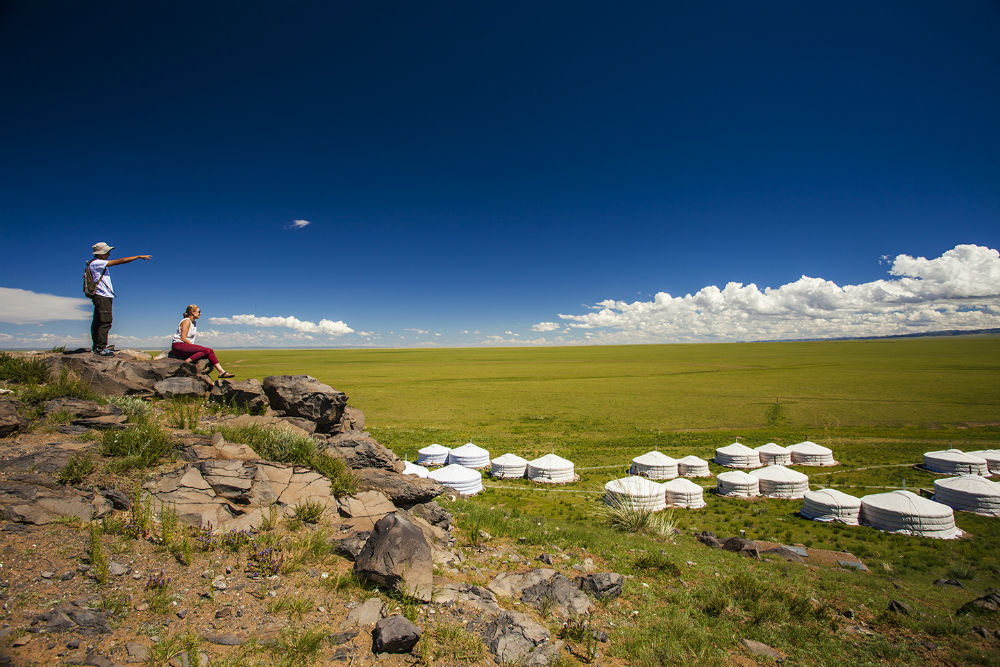 a group of luxury tents in the green grasslands of the Gobi, with two people overlooking the camp on a hill