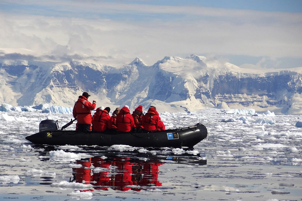 travelers in red winter coats rowing a zodiac boat amid floating ice and glaciers of Antarctica