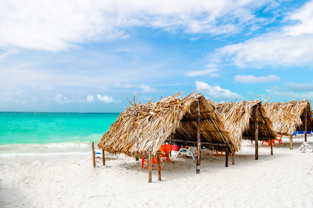 thatched bungalows on a white sand beach on Isla Baru, Colombia