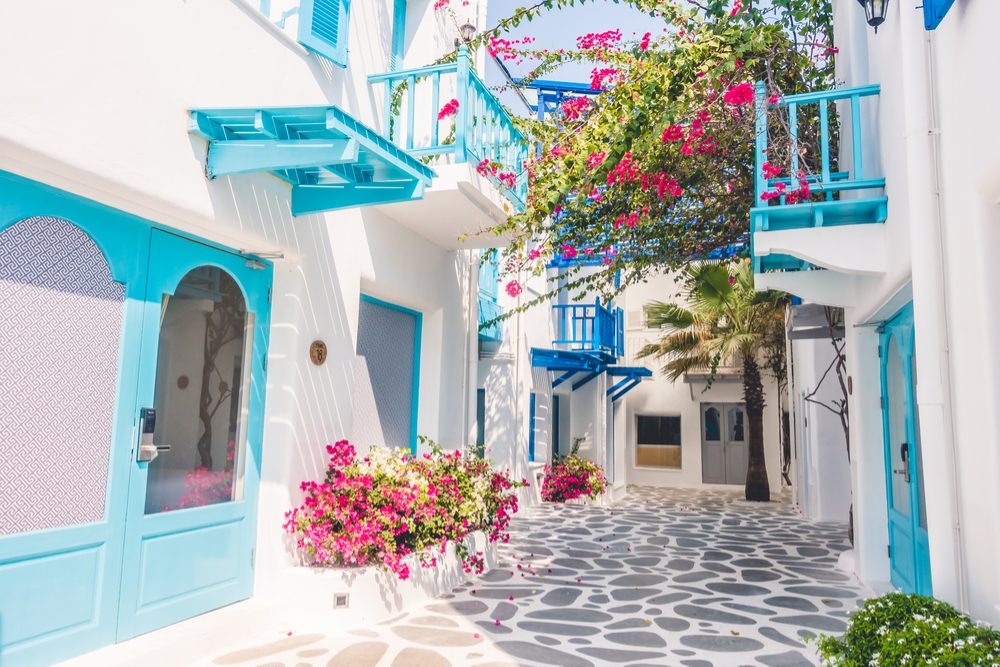 A village street of Santorini is bright white and blue, with pops of pink bougainvillea flowers