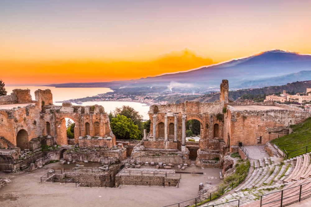 The Greek Theater of Taormina as the sun sets behind the smoking Mt. Etna, Sicily, Catania, Italy
