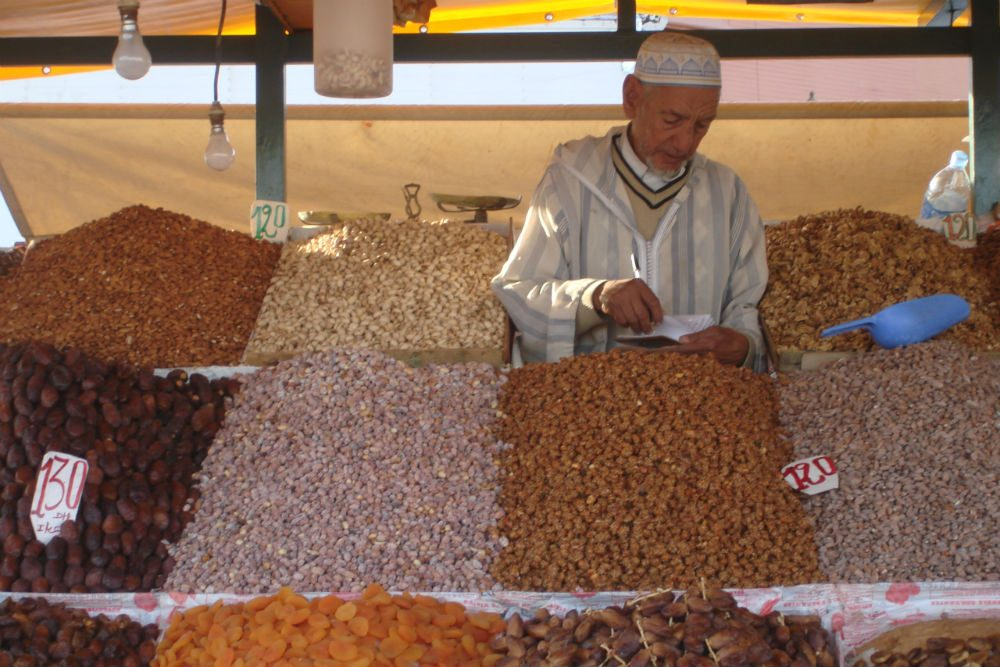man selling fruits and nuts in Marrakech Morocco market