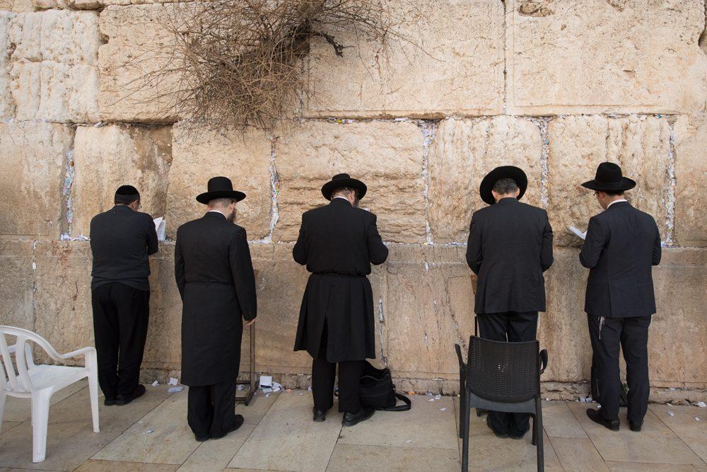 Men praying at the Western Wall Jerusalem Israel