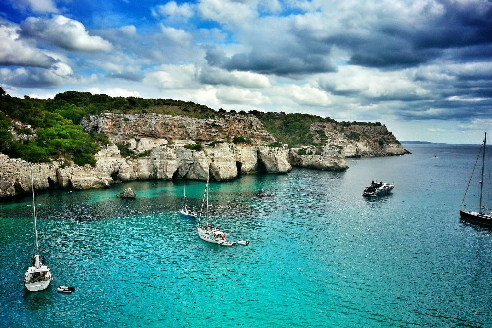 sailboats moored in turquoise water off a rocky shore in Menorca Spain