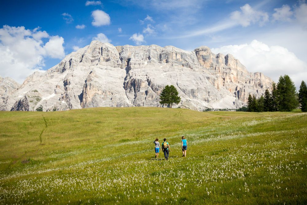 green meadow with mountains in bakcground and people hiking Alta Badia in Italy's Dolomites