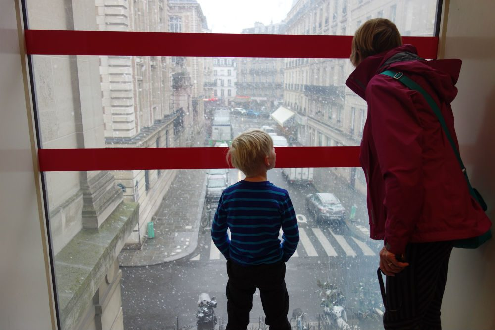 child and adult look out the window at the rain at the Musée des Arts et Métiers in Paris